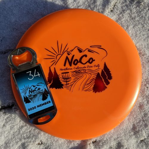 "Photo of the 2020 Northern Colorado Disc Golf membership pack. Shows an orange golf disc with a red Noco landscape graphic, and a metal bottle opener tag with a blue and black graphic with a white number ""34"" in the upper right corner."