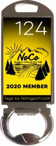 The 2020 membership tag for Northern Colorado Disc Golf. It is a rectangular, shiny metal bottle opener with a NoCo graphic and the number 124. The graphic has a yellow background that fades to black behind the white nubmer.